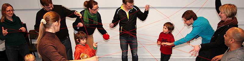 """Banner """"kontaktiv"""": Menschengruppe aus Kindern und Erwachsenen, die spielerisch mit einem roten Garn aus einem Wollkneuel miteinander verstrickt ist"""