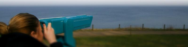 Banner Vision: Frau schaut durch Fernglas auf Meerküste