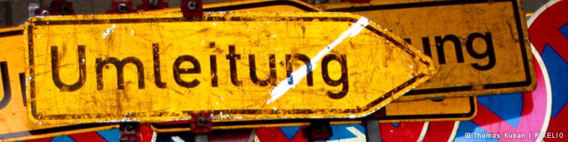 Bannermotiv: Ein verranztes Umleitungsschild auf einem Haufen abgenutzter Verkehrsschilder